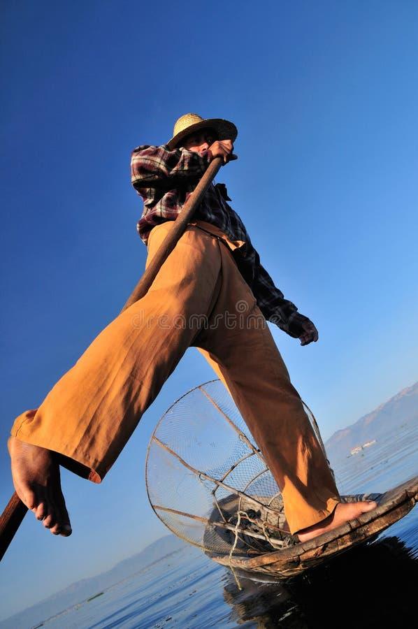 Burmese fisherman on boat catching fish. stock images