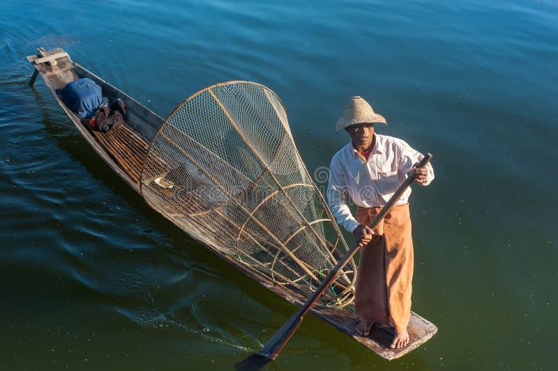Burmese fisherman catching fish in traditional way. Inle lake, Myanmar royalty free stock photography