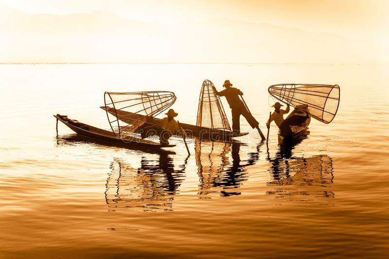 Burmese fisherman catching fish in traditional way. Inle lake, Myanmar. Burmese fisherman on bamboo boat catching fish in traditional way with handmade net. Inle stock photo