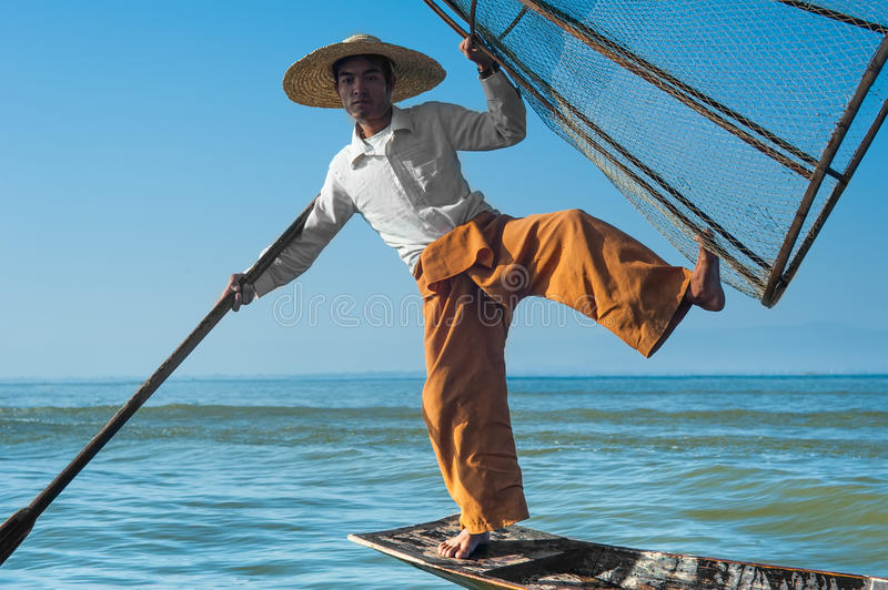 Burmese fisherman catching fish in traditional way. Inle lake, Myanmar. Burmese fisherman on bamboo boat catching fish in traditional way with handmade net. Inle royalty free stock images
