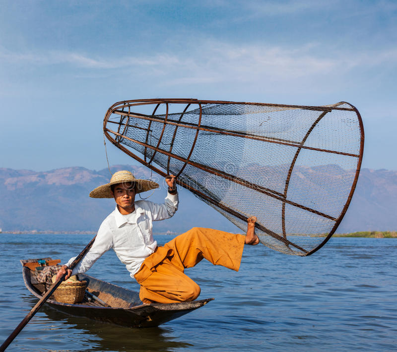 Burmese fisherman at Inle lake, Myanmar. Myanmar travel attraction landmark - Traditional Burmese fisherman with fishing net at Inle lake in Myanmar famous for stock images