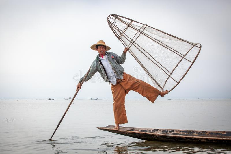 Burmese fisherman posing for tourists in a traditional fishing boat at Inle Lake, Myanmar royalty free stock photography