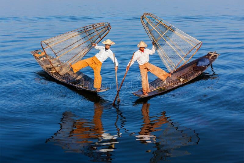 Burmese fishermen at Inle lake, Myanmar. Myanmar travel attraction landmark - Traditional Burmese fishermen balancing with fishing net at Inle lake in Myanmar stock images