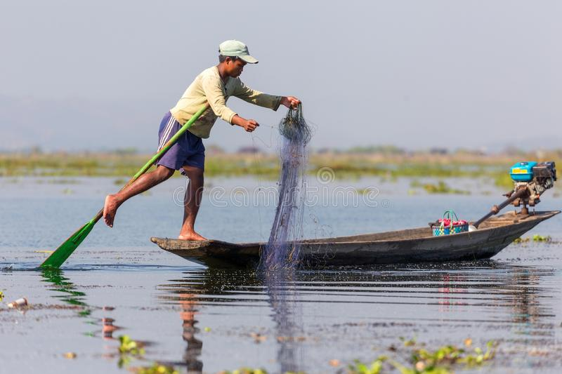 Burmese fishing technique. INLE LAKE, MYANMAR, JANUARY 26, 2015 : A fisherman showing the special technical rowing of the Burmese tradition using his leg to stock images