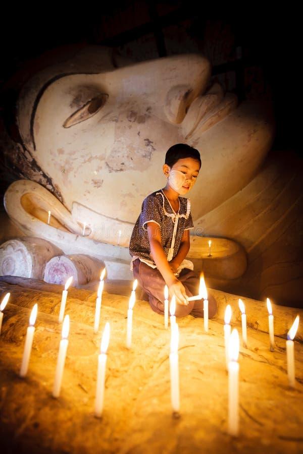 Burmese girl. BAGAN - MYANMAR - November 15, 2013: Unidentified Burmese girl praying with candle light in a Buddihist temple on November 15, 2013 in Bagan royalty free stock images