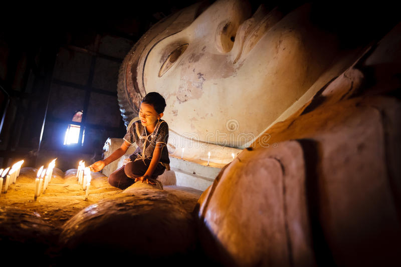 Burmese girl. BAGAN - MYANMAR - November 15, 2013: Unidentified Burmese girl praying with candle light in a Buddihist temple on November 15, 2013 in Bagan stock photos