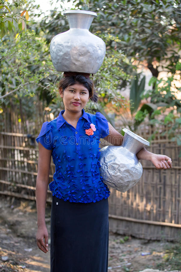 Burmese girl with big jugs with water. Mrauk U, Myanmar. MRAUK-U, MYANMAR - JANUARY 27, 2016: Unidentified Burmese girl with big jugs with water. The local royalty free stock image