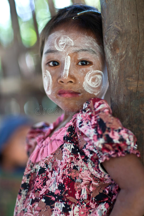 Burmese girl. MRAUK U, MYANMAR - JANUARY 06: Burmese schoolgirl with Thanaka paste on the face poses for a photo during the Manaw Festival on January 06, 2012 in stock photography