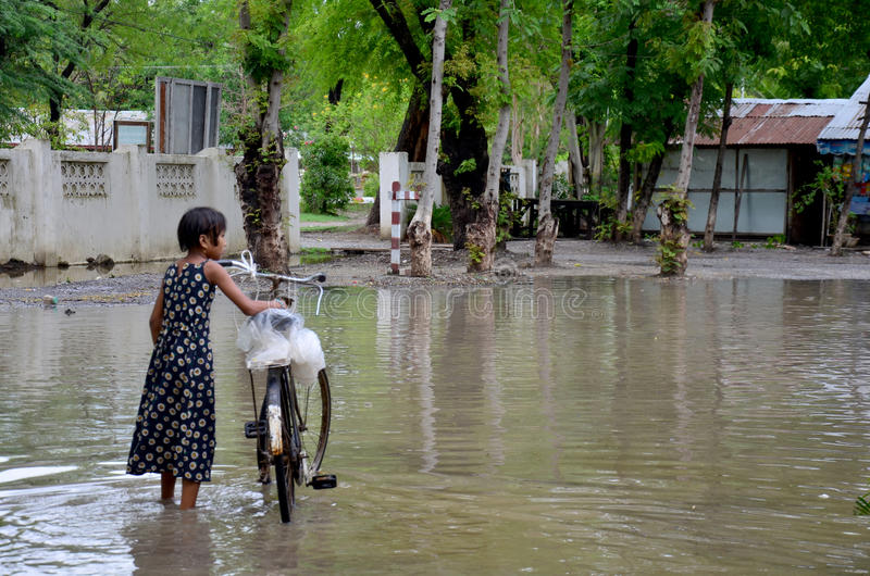 Burmese girl riding bicycle in flood area royalty free stock images