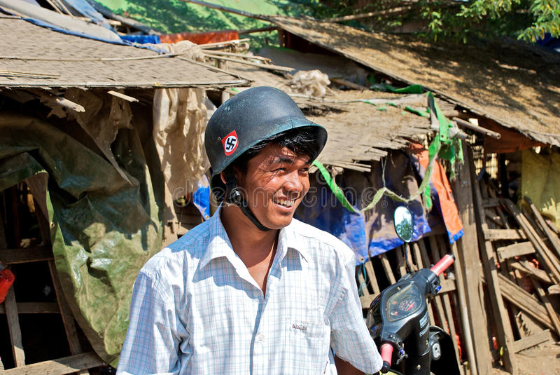 Burmese in the helmet. Burmese young man in a German helmet with a nazi symbol, the bazaar, Bagan, Spring 2012 royalty free stock image