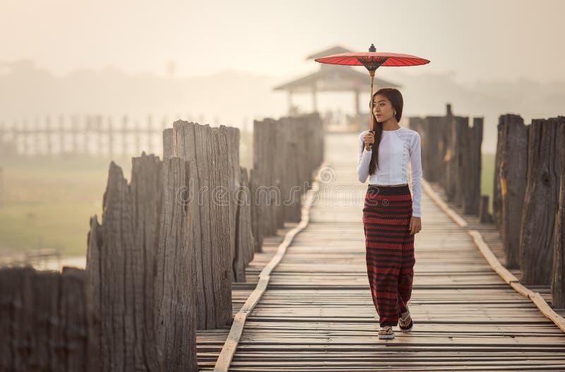 Burmese kvinna som rymmer det traditionella röda paraplyet royaltyfri foto