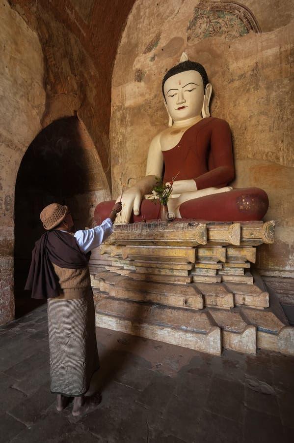 Burmese man brings religious offerings to Buddha statue. BAGAN, MYANMAR - 14 JAN, 2014: Unidentified Burmese man brings religious offerings to Buddha statue royalty free stock image