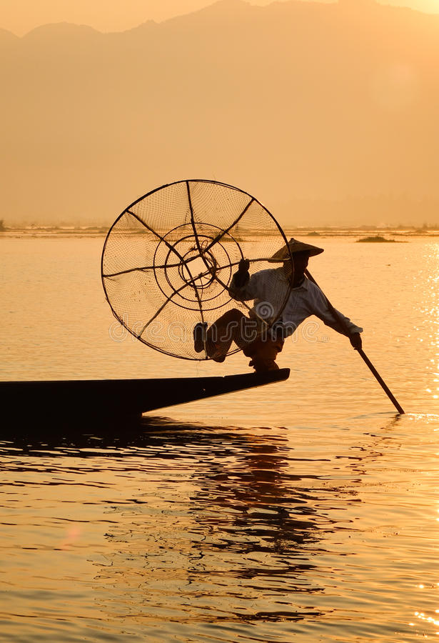 Burmese man catching fish on Inlay lake in Shan, Myanmar.  stock photos