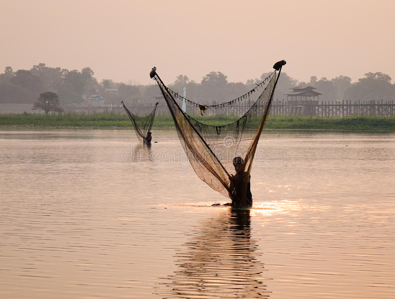 A Burmese man catching fish on the river in Mandalay, Myanmar.  stock images