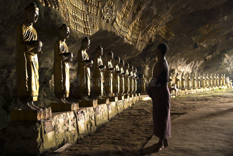 Burmese man praying in cave temple. Burmese man praying in front of row of golden buddhas in cave, Hpan, Myanmar royalty free stock photo