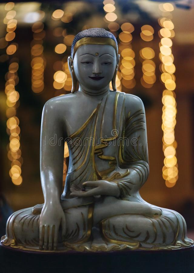 Burmese marble Buddha with city lights. Buddha`s figure made of marble in the Burmese style against the background of city lights stock image
