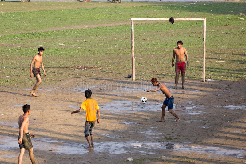 Burmese men playing football. AMARAPURA, MYANMAR, JANUARY 18, 2015: Burmese young men are playing football near the Ubein bridge in Amarapura, Myanmar (Burma stock images