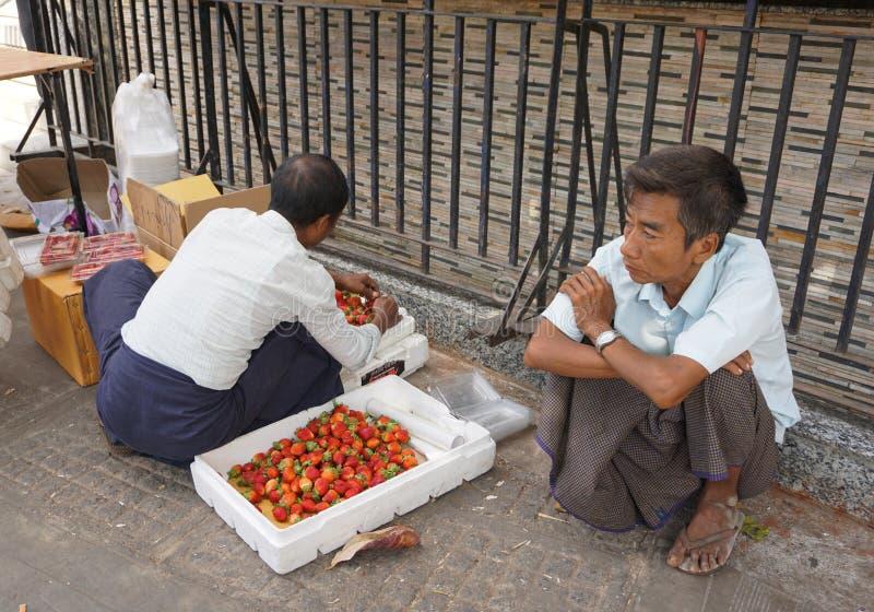 Burmese men selling fresh fruits at Bogyoke market. Yangon, Myanmar - Jan 14, 2015. Burmese vendors selling fresh fruits at Bogyoke market in Yangon, Myanmar royalty free stock images