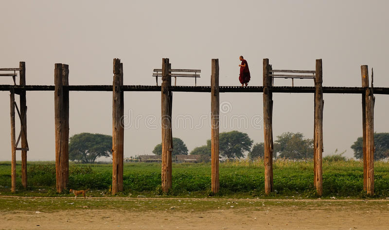 Burmese monk in red clothes walking on Ubein Bridge royalty free stock images