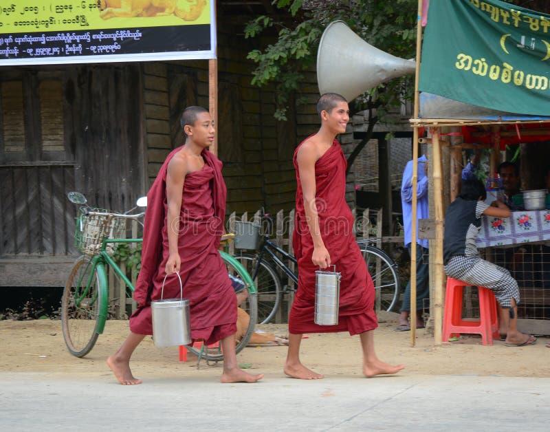Burmese monks walking morning alms. BAGAN, MYANMAR - OCT 1, 2015. Burmese young novice monks walking morning alms in Old Bagan, Myanmar. 89% of the Burmese stock photos