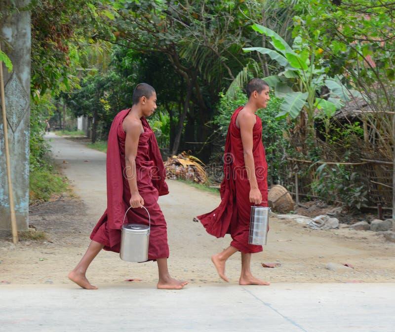 Burmese monks walking morning alms. BAGAN, MYANMAR - OCT 1, 2015. Burmese young novice monks walking morning alms in Old Bagan, Myanmar. 89% of the Burmese stock images