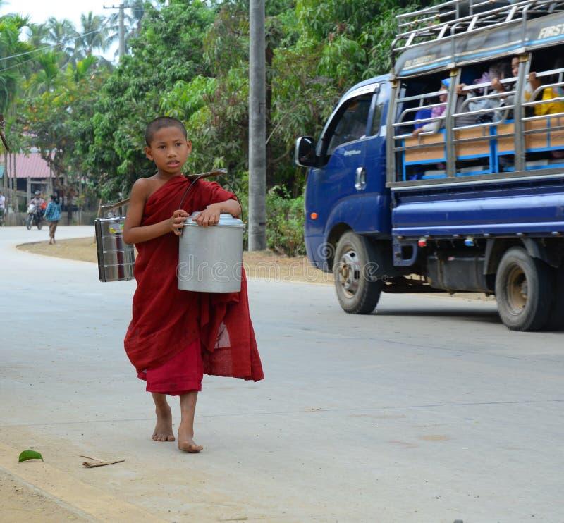 Burmese monks walking morning alms. BAGAN, MYANMAR - OCT 1, 2015. Burmese young novice monks walking morning alms in Old Bagan, Myanmar. 89% of the Burmese royalty free stock photos