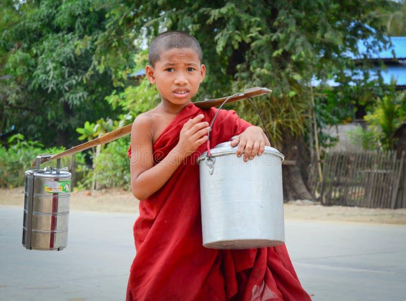 Burmese monks walking morning alms. BAGAN, MYANMAR - OCT 1, 2015. Burmese young novice monks walking morning alms in Old Bagan, Myanmar. 89% of the Burmese royalty free stock photography