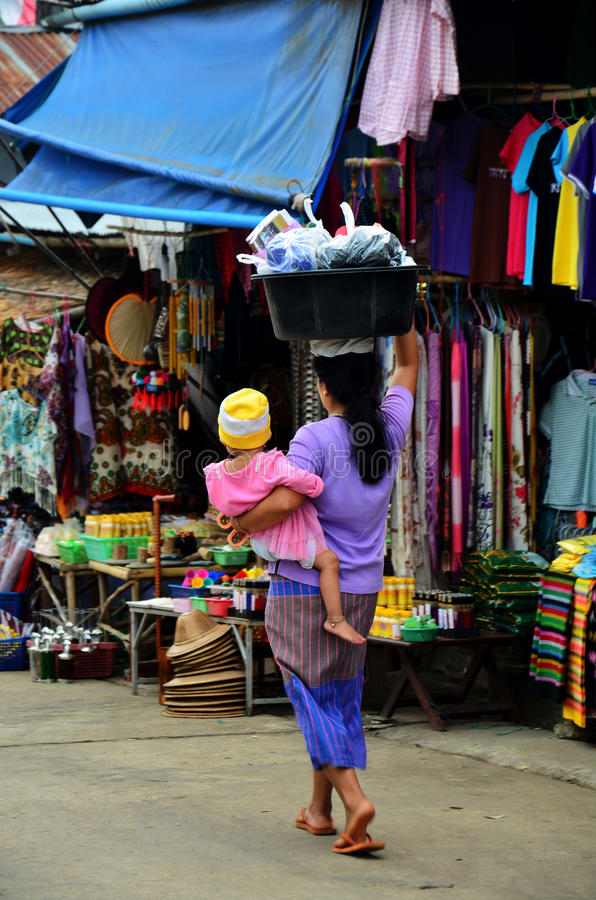 Burmese Mother hold the baby and carrying basin plastic on her h. Ead walking in market time at Sangkhlaburi on December 4, 2015 in Kanchanaburi, Thailand stock photography