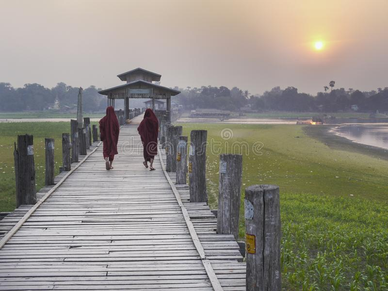 Burmese munkar som går över bron för U Bein på solnedgången royaltyfri fotografi