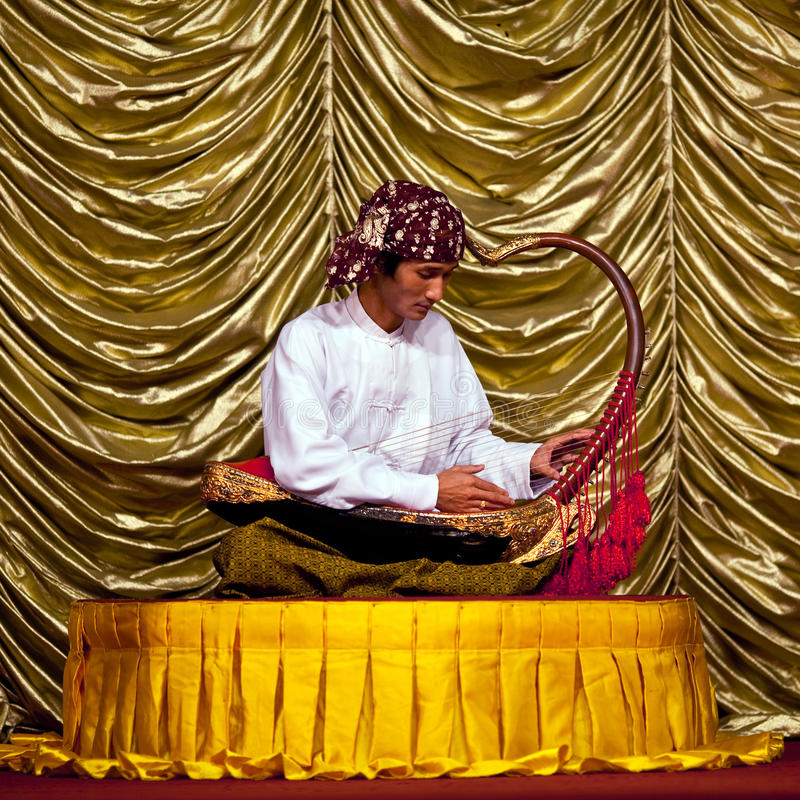 Burmese Musician. YANGON, MYANMAR - JANUARY 25, 2011: Musician with Harp plays on the evening show at Karaweik Hall. The Harp (Saung-Gauk) is a traditional royalty free stock image