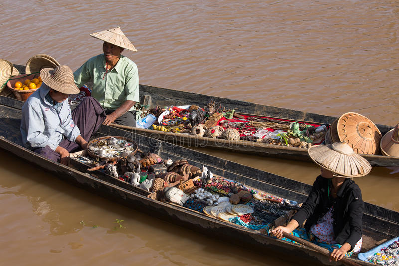 Burmese people on small long wooden boat selling souvenirs, trinkets and bijouterieat the floating market on Inle lake, Myanmar. INLE LAKE, MYANMAR - JANUARY 14 stock photography