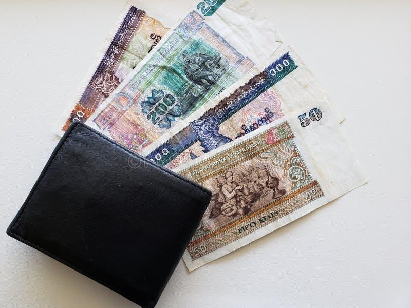 Burmese sedlar av olika valörer och svart piskar plånboken royaltyfri bild