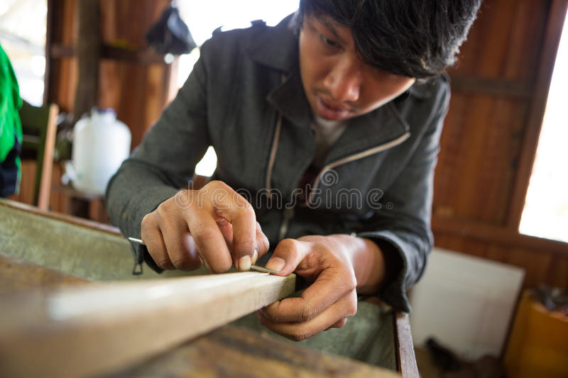Burmese silver worker scrapes a silver chain royalty free stock photo