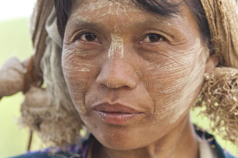 Burmese woman. Portrait of a burmese woman with thanaka powdered face who works in the field royalty free stock photos