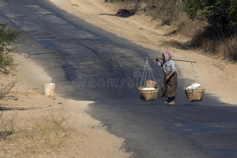 Burmese Woman - Myanmar (Burma). Burmese woman crossing a rural road in the countryside near Mandalay in Myanmar (Burma royalty free stock images