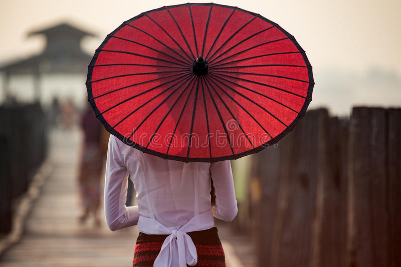 Burmese woman. Holding traditional red umbrella at U Bein Bridge stock photos