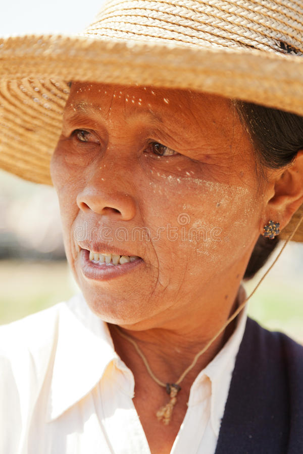 Burmese woman portrait. Heho, Myanmar - March 02, 2011 : Burmese woman shot near five day market on Inle Lake, she is wearing a typical hat and facial herb make stock photo
