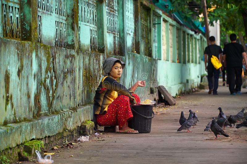 Burmese woman selling grains and seeds for pigeon food. stock photos