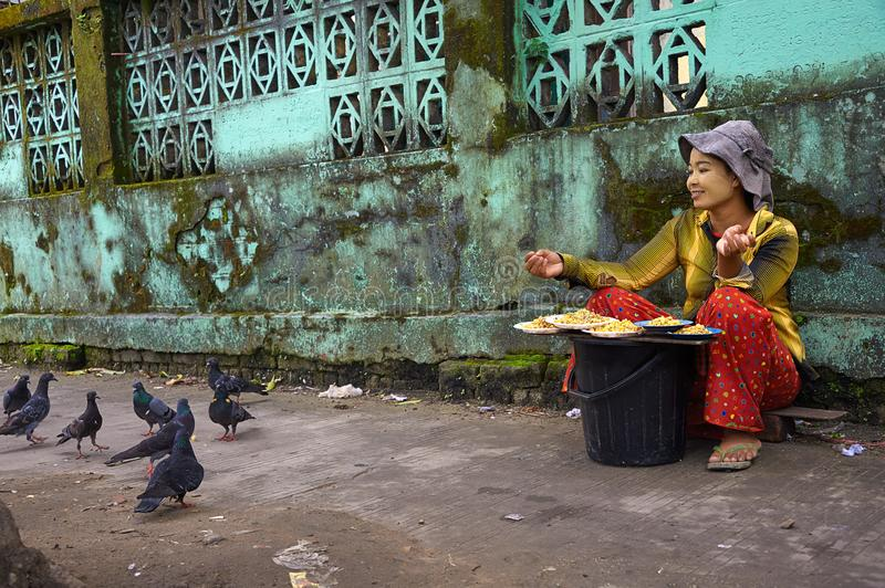 Burmese woman selling grains and seeds for pigeon food. stock photography