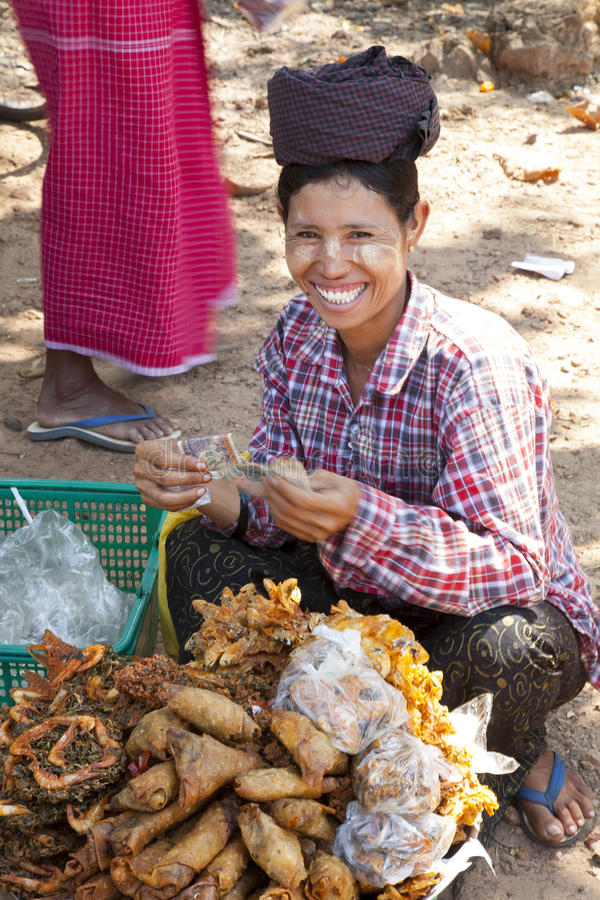 Burmese Woman Selling Snacks. A Burmese woman sells Burmese fried snacks at a festival in Myanmar royalty free stock images