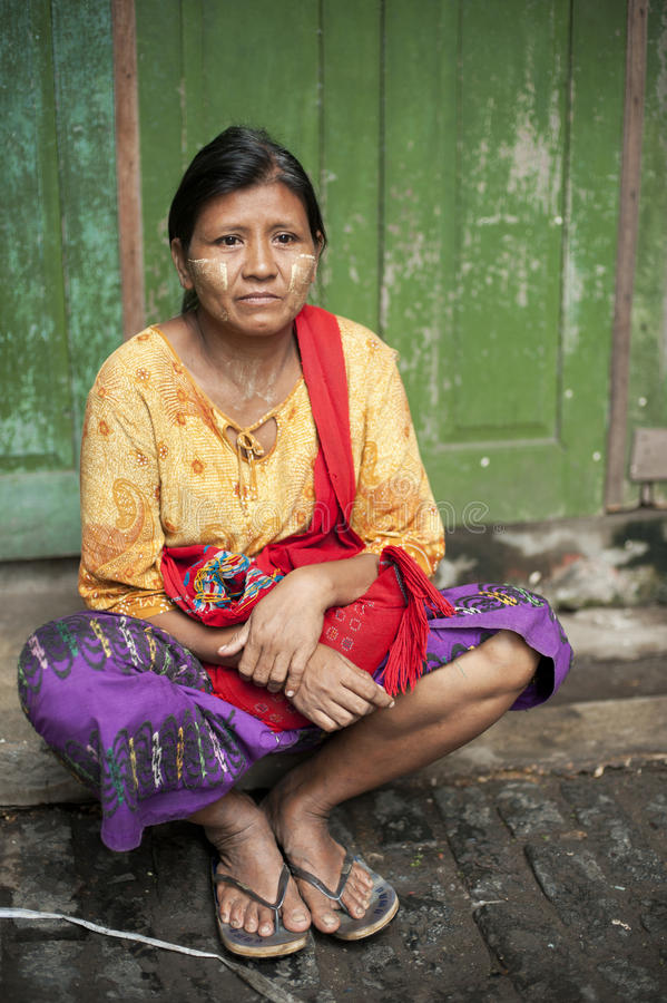 Burmese woman sitting in front of the door. Portrait of a middle age woman taken in Yangoon market. Myanmar opens up for tourists royalty free stock photos