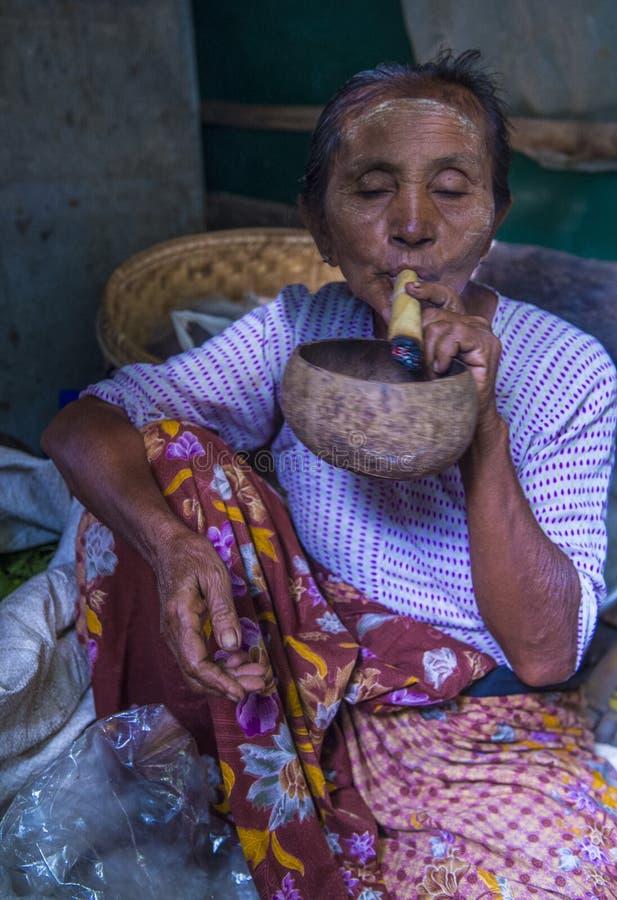 Burmese woman smoking a cheroot cigar. BAGAN, MYANMAR- SEP 04 : Woman smoking a cheroot cigar in market in bagan, Myanmar on September 04, 2017. Cheroot is a stock images