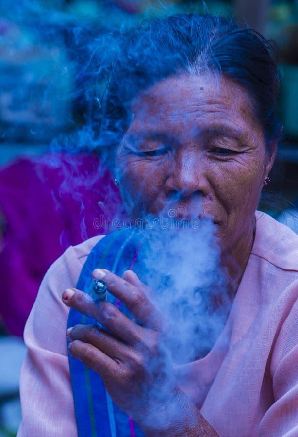 Burmese woman smoking a cheroot cigar. BAGAN, MYANMAR- SEP 04 : Woman smoking a cheroot cigar in market in bagan, Myanmar on September 04, 2017. Cheroot is a stock image