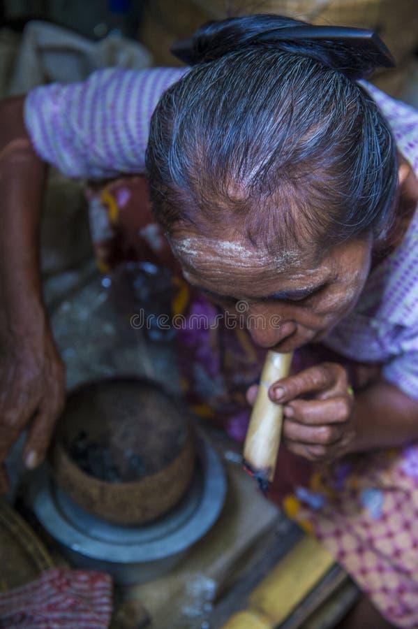 Burmese woman smoking a cheroot cigar. BAGAN, MYANMAR- SEP 04 : Woman smoking a cheroot cigar in market in bagan, Myanmar on September 04, 2017. Cheroot is a royalty free stock images