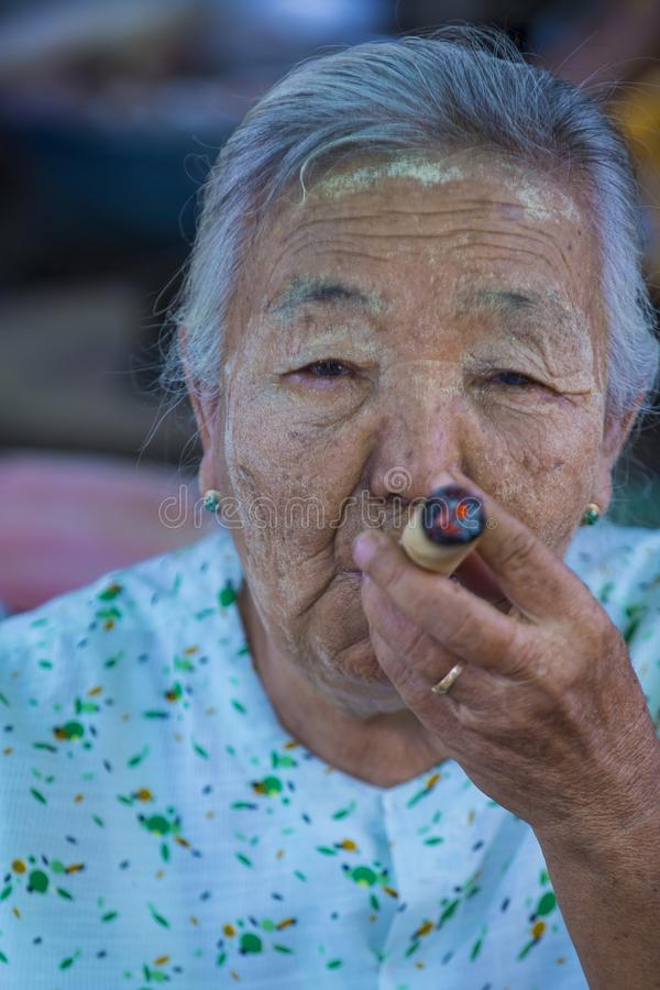Burmese woman smoking a cheroot cigar. BAGAN, MYANMAR- SEP 04 : Woman smoking a cheroot cigar in market in bagan, Myanmar on September 04, 2017. Cheroot is a stock photo