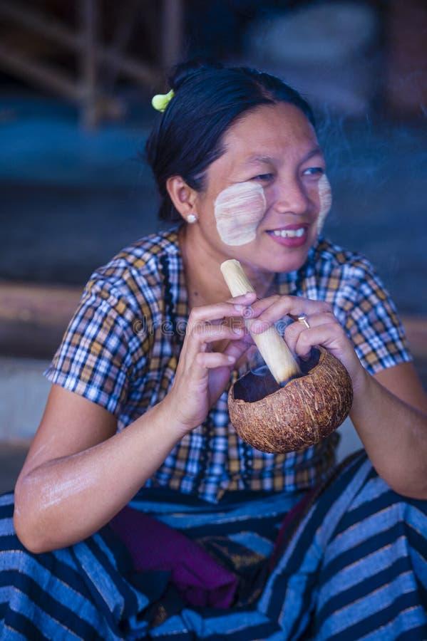 Burmese woman smoking a cheroot cigar. BAGAN, MYANMAR- SEP 04 : Woman smoking a cheroot cigar in market in bagan, Myanmar on September 04, 2017. Cheroot is a royalty free stock photos