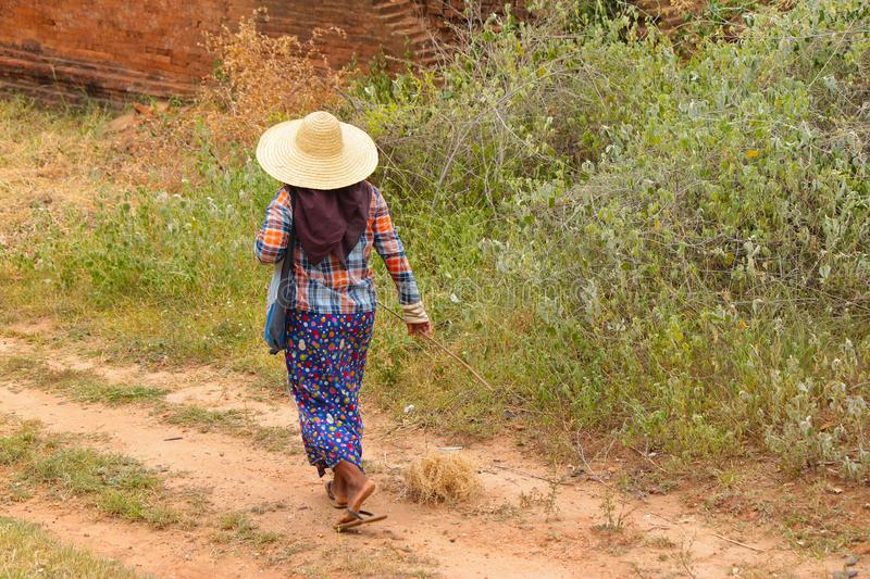 Burmese woman walking barefoot with her typical and colorful clothing in Bagan, Myanmar Burma. royalty free stock images