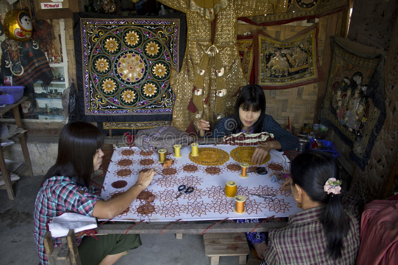 Burmese woman at work sewing beads. The work of an artisan that has sew the canvas with beads. Sewing beads onto tapestry has an ancient history estimated to royalty free stock photo