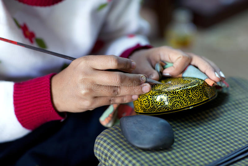 Burmese woman working in a factory of lacquer. In Nyaung U village, Myanmar. Lacquerware includes boxes, tableware, buttons and even coffins stock photography