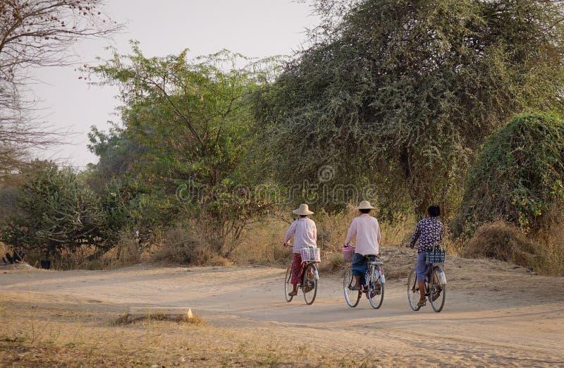 Burmese women biking on rural road in Bagan, Myanmar.  royalty free stock images